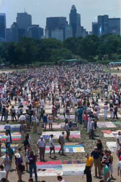25 Jun 1988, Manhattan, New York City, New York State, USA --- Original caption: New York: New York skyline looms in the background, as residents examine the New York Memorial Quilt on Central Park's Great Lawn. The quilt consists of close to 1,500 panels bearing the names and images of people who have died of AIDS. --- Image by © Bettmann/CORBIS